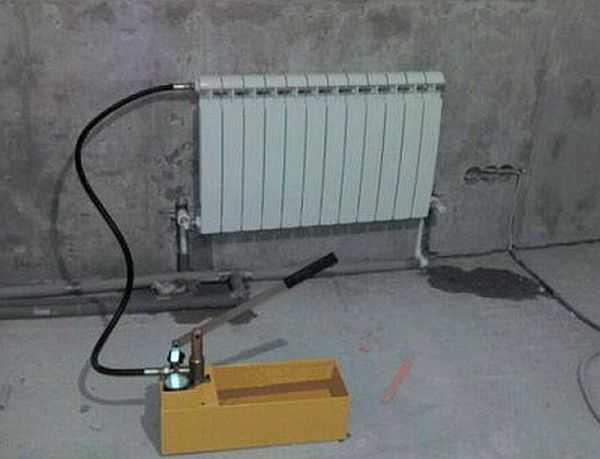 Опрессовочный аппарат для проверки герметичности системы. Лужи на полу — свидетельство того, что придется устранять течь